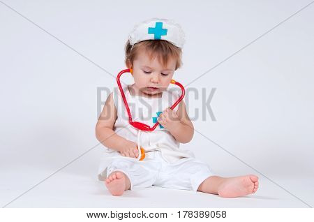 A cheerful laughing baby girl playing as a doctor with a stethoscope