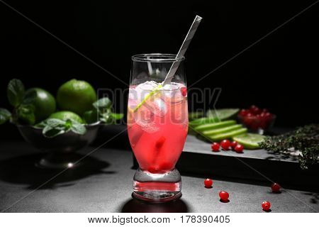 Refreshing cocktail with cranberry on dark table