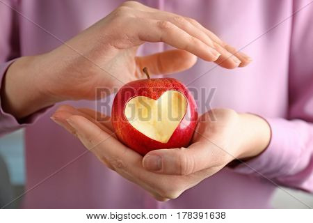 Woman hands holding fresh red apple with heart-shaped cut out, closeup