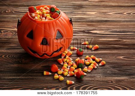 Tasty candies and Halloween decor on wooden background