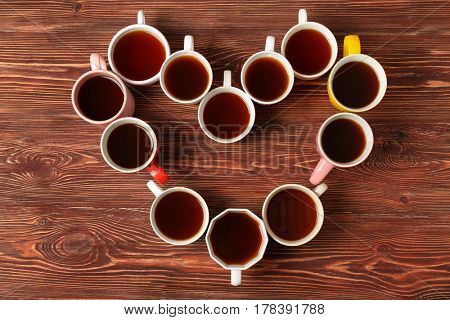 Delicious tea in cups forming heart on wooden background