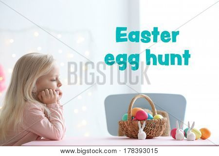 Cute little girl with colorful eggs at home. Text EASTER EGG HUNT on background