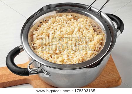 Colander with brown rice in saucepan on wooden board