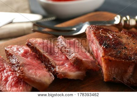 Sliced pieces of delicious medium rare steak on wooden board