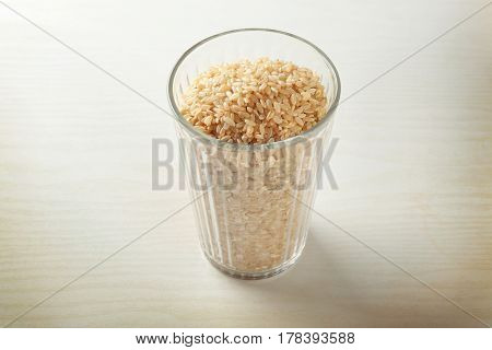 Faceted glass full of brown rice on white table