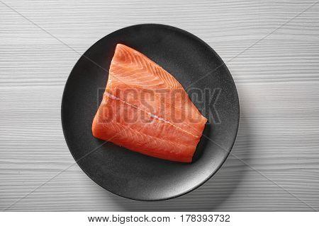 Fresh salmon fillet on black plate