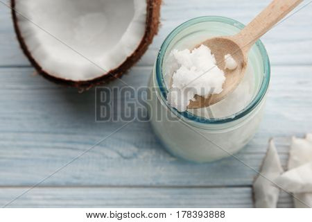 Spoon with fresh coconut oil taken from glass jar on light wooden background