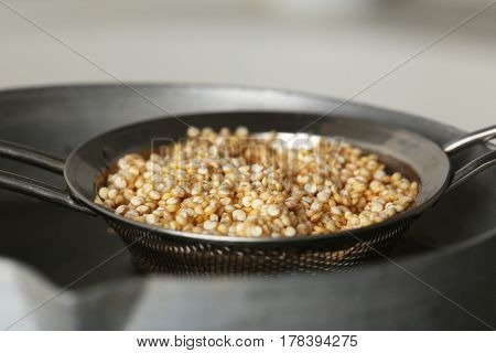 Sieve with quinoa seeds in saucepan, closeup
