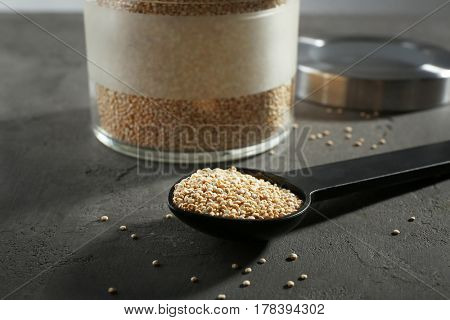 Spoon with quinoa seeds on grey table