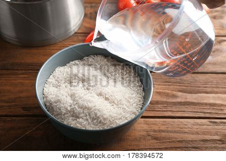 Pouring water into bowl with rice on kitchen table