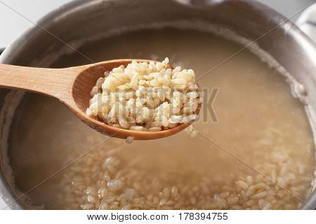 Spoon with brown rice over saucepan