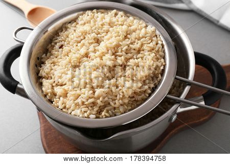 Colander with prepared brown rice in saucepan