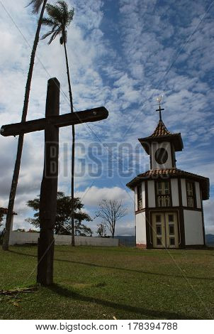 Our Lady of the Rosary Church, located in Milho Verde, Minas Gerais. Mineira Church. Church of the nineteenth century. Blue sky. Church on a hill. Cross and Church.