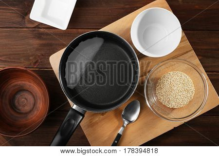 Kitchen utensils and quinoa seeds in bowl on wooden table