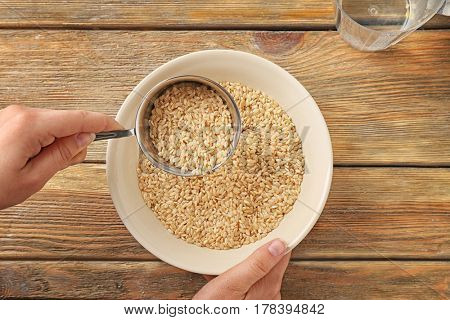 Female hand filling bowl with brown rice on wooden background