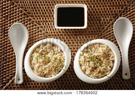Two bowls with brown rice on wicker mat background