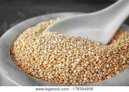 Organic quinoa seeds and spoon in bowl, closeup
