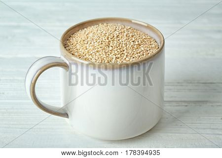 Organic quinoa seeds in mug on wooden background