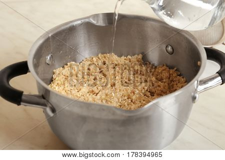 Pouring water into pan with brown rice, closeup