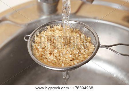 Washing raw brown rice in colander over kitchen sink