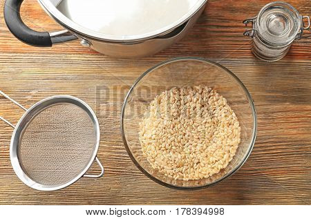 Glass bowl with brown short grain rice on wooden table