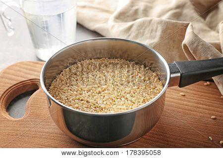 Pan with brown short grain rice on cutting board