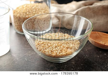 Glass bowl with brown short grain rice on grey kitchen table