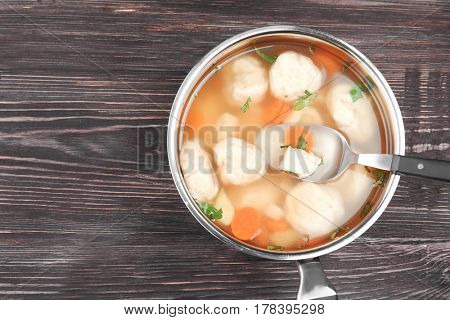 Stewpan with delicious chicken and dumplings on wooden table