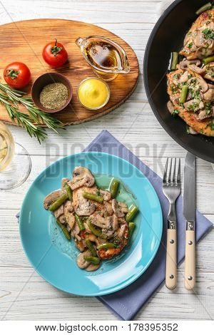 Plate with delicious chicken marsala and mushrooms on table