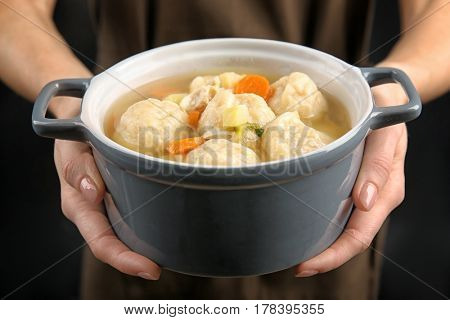 Female hands holding ceramic pan with delicious chicken and dumplings
