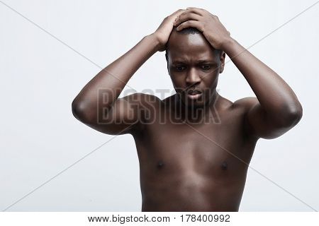 Negative emotion concept stressed man. Closeup headshot very sad depressed disappointed gloomy young man head on hands screaming in despair isolated on grey wall background. Human emotion facial expression reaction