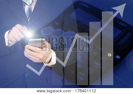 Double Exposure Of Businessman Using Smart Phone With Growth Graph Chart And Blurred Stacks Of Coins