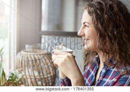 Close up portrait of attractive female international student having rest during break in coffee shop waiting for friends meeting sitting near copy space area for your advertising messages or content