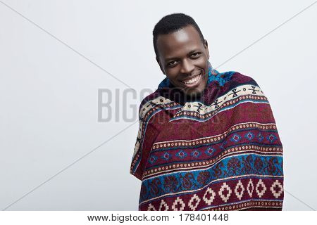 Head shot portrait of young happy African American guy looking friendly smiling or laughing at the camera. Covered with ethnic blanket and moving on a gray background