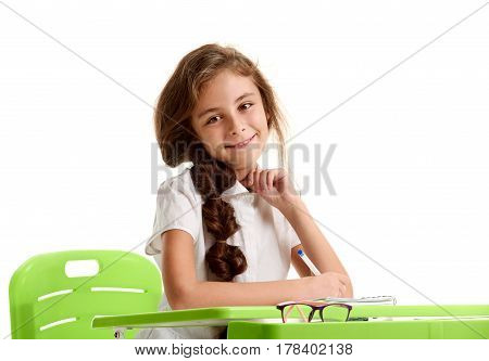Portrait of beautiful young schoolgirl making notes during lesson