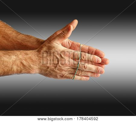 Hand with a rubber band. Isolated on a gray