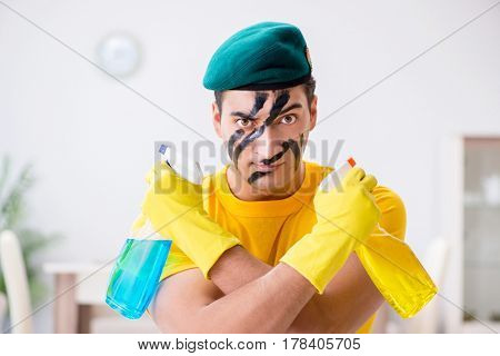Man in military style cleaning the house