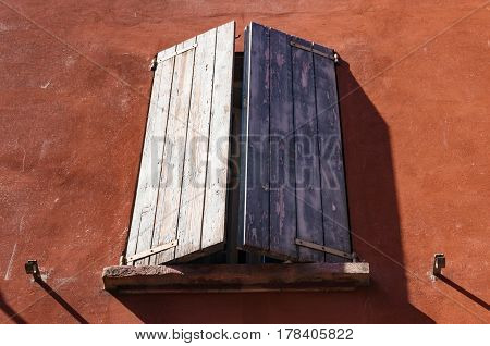 Window With Wooden Sun Blinds On Terracotta Wall