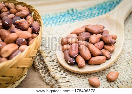 Raw peanuts or arachis in wooden spoon on sack