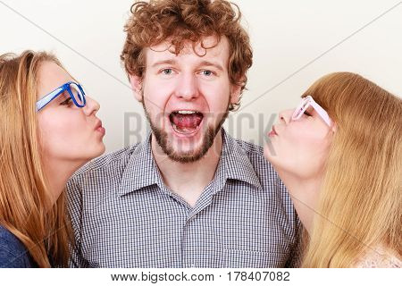 Two pretty young women in glasses kissing handsome man. Love triangle.