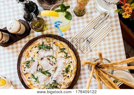 Pizza with cheese, mushrooms and meat, on served table with plaid tablecloth