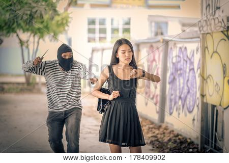 Street thief holding knife and trying to steal and run away the shoulder bag while woman looking watch Vintage tone style