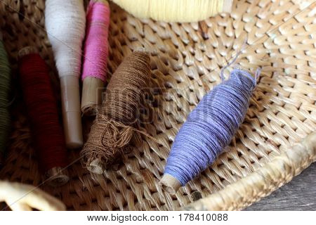 a colorful bobbins of thread in basket