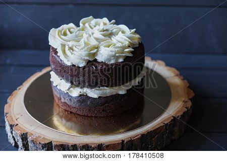 Beautiful biscuit cake with white cream on wooden tray
