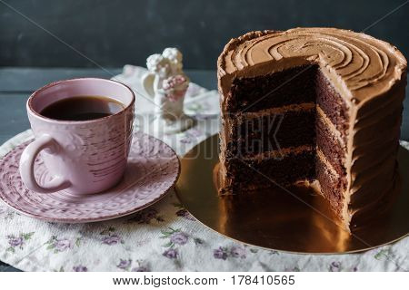 Delicious cake in chocolate sauce and piece is cut off, cup of tee, on tender tablecloth