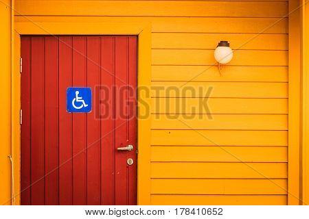 Blue handicapped wheelchair sign on door of public toilet outdoor WC restroom