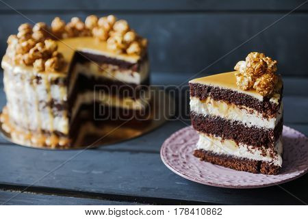 Delicious cake with caramel popcorn and caramel sauce and plate with slace of this cake