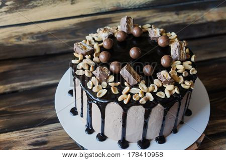 Delicious cake with peanut and dark chocolate sauce and pieces of Snickers candy and chokolate balls