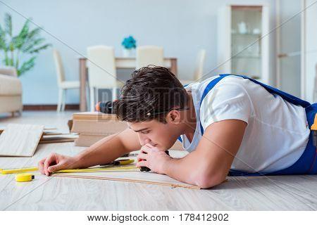 Repairman laying laminate flooring at home