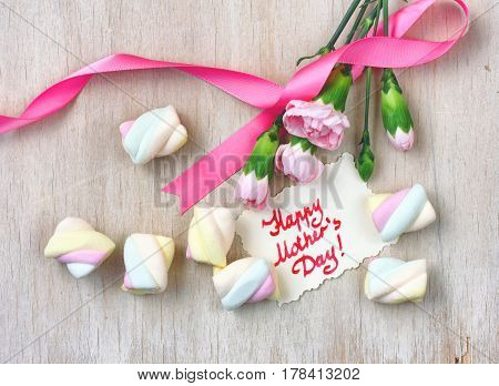 Mother's day card pink carnations with ribbon on a wooden table note with the inscription